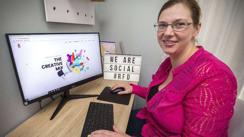 Lainey Founder of Rocket Fuel Design smiling at her Desk