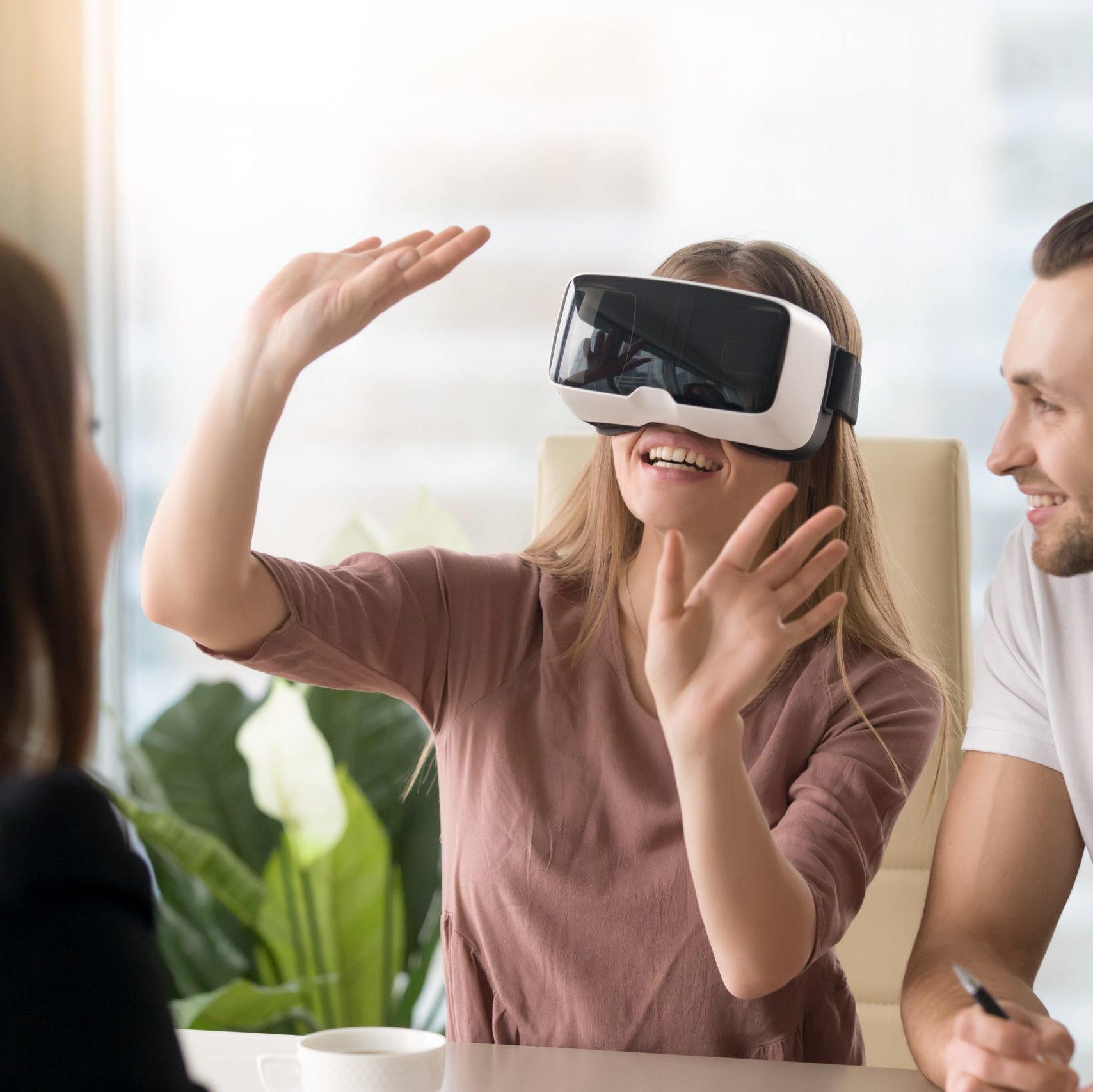 Woman wearing virtual reality headset, team developing VR glasse