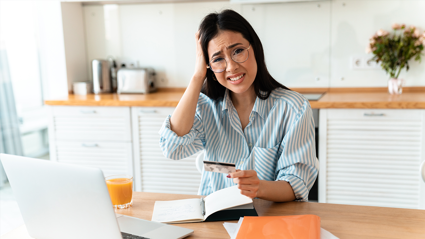 Women confused at laptop with credit card in hand
